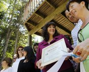 Sylvie Nelson, executive director for the Saranac Lake Area chamber of commerce, center, attends a ribbon cutting ceremony for a yoga studio June 18 in Saranac Lake, N.Y. Nelson, a 44-year-old white woman, keeps getting snared at the Canadian border because she apparently shares some key identifying information with a black man, possibly from Georgia, who is in trouble with the law.