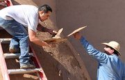 Marcos Martinez, left, and Steven Torres, parishioners of San Francisco de Asis Church in Ranchos de Taos, N.M.,apply mud to the thick adobe walls of the church June 14 as part of an annual ritual that has been done for nearly 200 years.