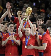 Spain's Andres Iniesta, center, holds up the World Cup trophy as he celebrates with teammates after a 1-0 finals victory Sunday over the Netherlands in Johannesburg.