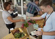 Rita Haswood, left, purchases peppers from West Junior High School ninth-grade student T.J. Everett in this July 12 photo. The student gardeners are taking part in the Our Local Food Program.