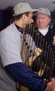Former New York Yankees manager Joe Torre, left, and team owner George Steinbrenner hold the World Series trophy after the Yankees won it on Oct. 27, 1999. Steinbrenner, who rebuilt the New York Yankees into a sports empire, died on Tuesday in Tampa, Fla.