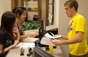 Kansas University sophomores Tan Ying Li, left, and Mabel Kok, both from Penang, Malaysia, receive financial aid forms from student adviser Brett D'Augustine, of Atchison, July 15 at the financial aid office in Strong Hall.