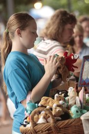 Sarah Stringer, 15, of Lawrence, looks at the selection of plush toys at Prairie Patches, 821 Mass., this morning at the Downtown Sidewalk Sale.