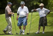 Noon Group members Don Sambol Sr., left, and George Bocquin, right, wait as Dick Logan steps up to tee off on the second hole Wednesday at Alvamar Country Club.