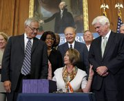 House Speaker Nancy Pelosi, D-Calif., center, reaches out to Rep. Barney Frank, D-Mass., left, and Sen. Christopher Dodd, D-Conn., right, after signing the financial reform legislation during an enrollment ceremony Thursday on Capitol Hill in Washington.