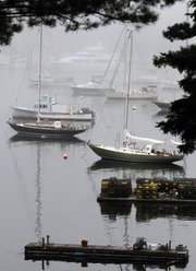 Boats are seen in the fog-shrouded Northeast Harbor in Maine. The president is scheduled to visit Mt. Desert Island this coming weekend.