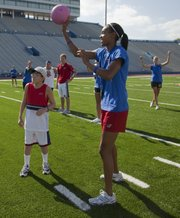 Special Olympian George Wedge, left, and Kansas University student-athlete Tayler Tolefree, play kickball together during the Big 12 Special Olympics Kickball Classic on Saturday. The event was part of the inaugural Big 12 Leadership Summit at KU.
