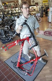 Curtis Martell, director of the Free State Racing Team of Lawrence, shows a bicycle that was destroyed when a pickup truck driver ran a cyclist off the road.