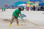 An oil cleanup worker rakes the sand Sunday in Orange Beach, Ala. BP hopes to keep using its giant stopper to block oil from reaching the Gulf of Mexico until it plugs the blown-out well permanently.