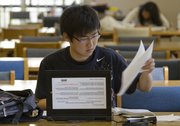 Shun Xi, an electrical engineering student, studies in Anschutz Library with the aid of a rental laptop the library offers.