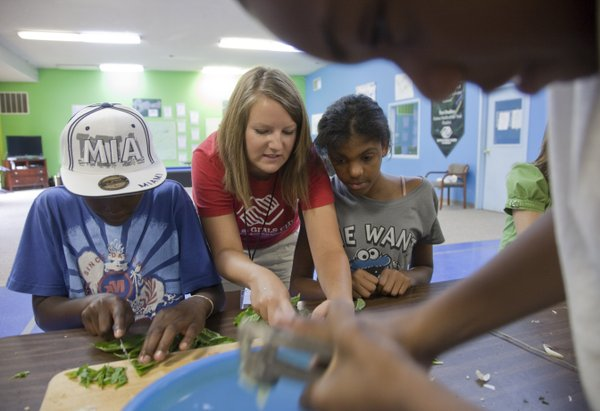 At center, Boys and Girls Club staffer Mackenzie Kerns teaches Cameron Clark, 12, left, and Jasmine Cook, 12,  how to prepare basil for a pizza sauce, Tuesday, July 20, 2010. The sauce will be used on pizzas that will be served in the club's first Pizza Garden Cafe, which will be open Tuesday, July 27. At top, Tavion Doleman, 11, presses some garlic.