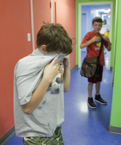 A Boys and Girls Club member dabs his eyes with his shirt after cutting onions at the club Tuesday, July 20, 2010. He was among 25 students who prepared a pizza sauce with vegetables and herbs grown in the club's garden.