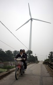 Men ride a motorcycle near the wind power generator in Nantong, east China's Jiangsu province, in this June 2, 2009, file photo. China has overtaken the United States as the world's largest energy consumer, the International Energy Agency said Tuesday. China immediately questioned the calculation.