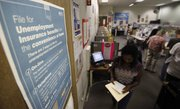A poster that explains ways to file for unemployment insurance benefits is shown as job seekers look for work Tuesday at the JobTrain employment office in Menlo Park, Calif. The Senate passed a measure to restore jobless benefits by a 59-39 vote Wednesday.