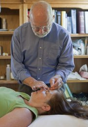 Jeff Nichols, M.D., provides an acupuncture procedure for sinus relief to Deb Carter. Nichols offers complementary medicine at his office at 1023 Ky.