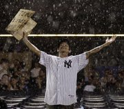 A Yankees fan stands in a downpour during a rain delay in the fifth inning. The Yankees beat the Royals, 7-1, Friday at Yankee Stadium.