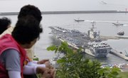 "South Koreans watch the Nimitz-class USS George Washington leaving for joint military exercises today at the Busan port in Busan, south of Seoul, South Korea. The massive nuclear-powered U.S. supercarrier began maneuvers today with ally South Korea in a potent show of force that North Korea has threatened could lead to ""sacred war."""