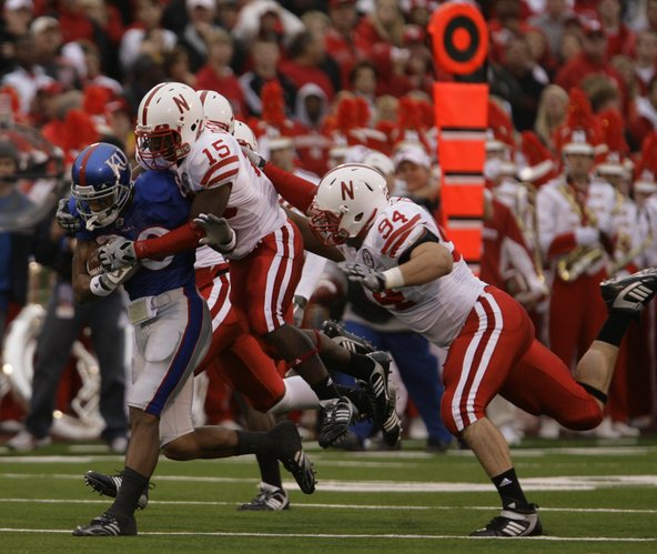 Nebraska defenders Alfonzo Dennard (15) and Jared Crick (94) drag down Kansas receiver Dezmon Briscoe last season in Lawrence.