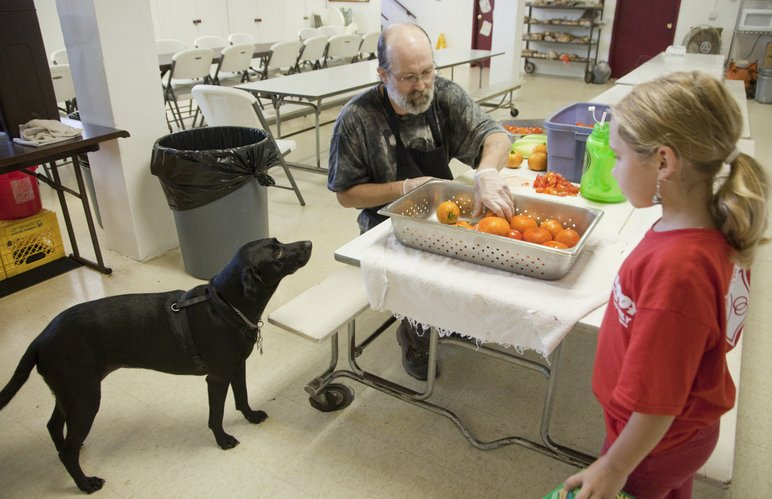 With his service dog Gabbie at his side, Dwight Sexton, volunteers in the Salvation Army kitchen cutting up tomatoes for lunch Monday, July 26, 2010. At right is Donna Brauer, 9, daughter of Diana Brauer, the food services director at The Salvation Army.