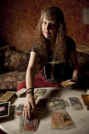 Tarot card reader Kacey Carlson, 44, of the Village Witch, 311 N. Second St., sometimes will use tarot cards to read travel ambitions of customers.