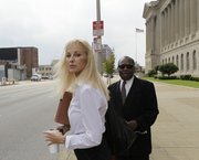 Karen Cunagin Sypher stands with Rev. William Franklin outside the federal courthouse after listening to a day of testimony in her extortion trial Wednesday in Louisville, Ky.