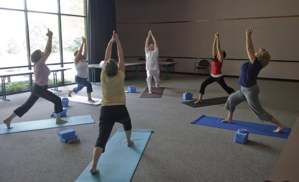 Yoga instructor Tanya McNeely, second from right, leads employees at Golf Course Superintendents Association of America, through a lunchtime yoga class on Thursday, July 29, 2010. The company offers  yoga classes five times a week.