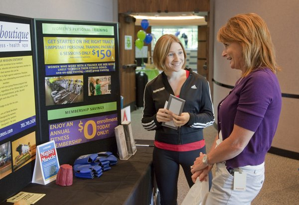 Katie Butler, fitness director at Body Boutique, left, visits with Becky Gonzales, director of human resources at Golf Course Superintendents Association of America, 1421 Research Park Drive, on Thursday, July 29, 2010, during a wellness fair. Representatives from 16 area organizations and companies were on hand to speak with GCSAA employees about community health and fitness programs.