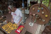 Artist Nick Schmiedeler works on old sign lettering in his backyard studio area with other pieces he has created for his yard art display at 710 Missouri.