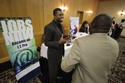 Cedric James, left, Admissions Director with MyComputerCareer.Com, meets with a prospective job applicant at a National Career Fairs Job Fair on July 20 in Plano, Texas. New jobless claims fell last week for the third time in four weeks, but remain above 450,000, where they have been all year.
