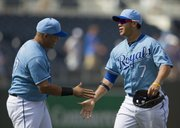 Kansas City's Gregor Blanco (7) and Brayan Pena celebrate the Royals' 5-4 victory over the Orioles on Sunday in Kansas City, Mo.