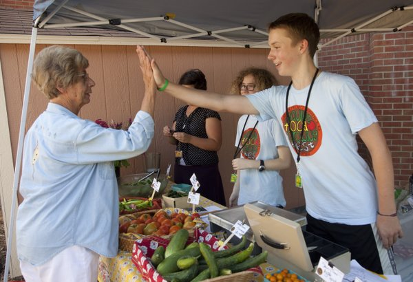 Barbara Thomas, a former West Junior High School teacher, gives a congratulatory high-five to ninth-grade student T.J. Everett, during a visit by Thomas to the school's farmers' market Monday, Aug. 2, 2010. So far, T.J. and five other students have worked on the garden this summer and made $1,700 through sales of produce and products. The money goes back into the garden.