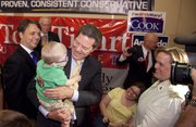Republican gubernatorial candidate, Sen. Sam Brownback picks up two-year-old Harrison Littlefield of Overland Park after speaking to those gathered at the Overland Park Marriott for a watch party organized by the Johnson County Republican Party, Tuesday, Aug. 3, 2010. At left is Lt. gubernatorial candidate and Kansas senator Jeff Colyer.