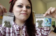 "Dani Geen holds 1 1/2 gram ""care packages"" of medical marijuana Tuesday at Harborside Health Center in Oakland, Calif. Until recently, the center had a program that gave out free weekly ""care packages"" to about 600 patients on unemployment or pensions."