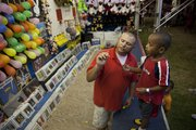 Carnival worker James Moore shows Keyon Free, 4, of Lawrence, how to hold a dart before an attempt to pop a balloon for a prize Thursday.