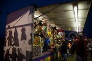 Shadows of hanging prizes are cast as carnival-goers browse the stands of Moore's Greater Shows Carnival on Thursday.