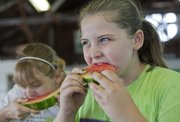 Alexis Leonard, 10, with the Eudora 4-H Club, chews through a slice of watermelon.
