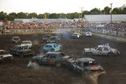 Cars slide in the mud during the first heat of the demolition derby.