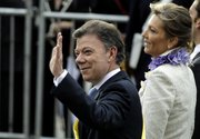Colombia's President Juan Manuel Santos waves to supporters next to his wife Maria Clemencia Rodriguez after his swearing-in ceremony Saturday in Bogota, Colombia.