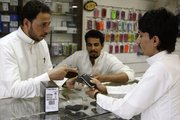 A Saudi customer is served Thursday in a mobile shop at a market in the capital Riyadh, Saudi Arabia. A preliminary agreement between the maker of the BlackBerry smart phone and the kingdom of Saudi Arabia will avert a ban on the phone in that country.