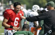 New York Jets quarterback Mark Sanchez, left, laughs with defensive coordinator Mike Pettine. Sanchez took a break between training-camp drills Wednesday in Cortland, N.Y.