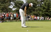 Phil Mickelson makes his putt on the fourth hole for par during the third round of the Bridgestone Invitational. Mickelson, who shot a 71 on Saturday in Akron, Ohio, is four strokes back going into today's final round.