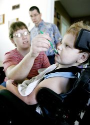 Beth Schneweis feeds her son Christopher, 5, some yogurt inside their Great Bend home as Christopher's dad, Mike, looks on in this July 27 photo. The couple are hoping to raise money for Christopher have a stem cell procedure for his cerebral palsy at a clinic in Germany.
