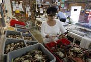 Connie Plessala organizes Louisiana blue crabs into bins Friday behind the counter of Big Fisherman Seafood in New Orleans. The rich fishing grounds of the Gulf of Mexico are beginning to reopen more than three months after crude began gushing from the sea floor. But those who harvest, process and sell the catch face a new crisis: convincing wary consumers it's not only delicious, but also safe.