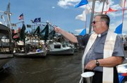 "The Rev. Jervis Burns blesses fishing boats docked Sunday in Bayou Delarge in Theriot, La., during the pre-shrimp season tradition known as the ""Blessing of the Boats."" Louisiana fishermen are hoping to once again fish for shrimp when the season officially opens next Monday."