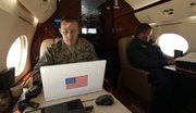 U.S. Air Force interpreter Tech. Sgt. Paul Shoop, left, works on his computer, as Russian Air Force Col. Alexander Vasiliev sits across the aisle as they fly aboard a civilian airplane playing the role of a hijacked airliner Sunday. The exercise is a first-of-its-kind joint exercise between the United States and Russia to test their coordinated response to a potential international hijacking.