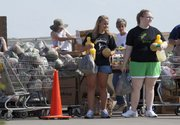 Volunteers Lindsay Ellis, center, and Olivia Johnson wait with food items for the next car to pull up during a distribution on Monday.