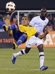 Brazil defender Dani Alves, left, goes up for a bicycle kick in front of U.S. midfielder Maurice Edu. Brazil upended the Americans, 2-0, Tuesday in East Rutherford, N.J.