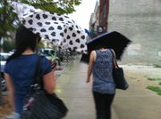 Two women have their umbrellas tossed by a strong wind as they walk the sidewalks downtown along Mass. St. Strong winds and rain blew into Lawrence around 5:15 p.m. Wednesday and sent people downtown scrambling for cover in the shower.