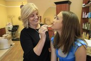 Marcia Butell, owner of Rejuvene Spa, applies lips gloss to Jessalyn Grant, 12.
