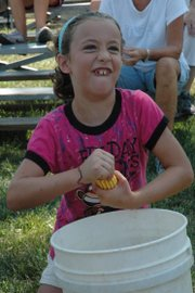 Lily Beach, 8, shells corn into a bucket Thursday afternoon at the 103rd annual Vinland Fair. Lily easily won the 8-9 year-old division.